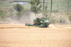 Moissonneuse dans un domaine moissonnant le blé Paysage photos stock