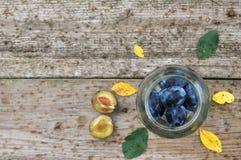 Moissonnez les prunes pourpres pour mettre en boîte dans un pot en verre sur des feuilles d'un fond en bois, de jaune et de vert  images libres de droits