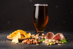 A moist glass of brown ale, with crisps, bacon, peanuts, hazelnuts and pistachios on a dark background. A moist glass of brown ale, with crunchy crisps, sappy stock image