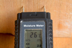 Moisture content. A meter with needle probes is used to determine the moisture content of a piece of new timber Royalty Free Stock Photography