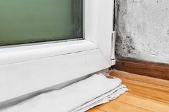 Moisture and mold -Problems in a house. Condensation cause mold and moisture in the house -Towel absorbs water from the window Royalty Free Stock Image