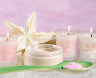 Moisturising Cream. With candles against a pink background Royalty Free Stock Image