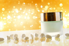Moisturizer concept jar closed yellow bokeh background with smal Royalty Free Stock Photography