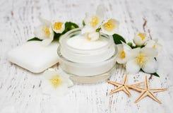 Moisturizers κρέμας προσώπου και σωμάτων με jasmine τα λουλούδια στο άσπρο W Στοκ Φωτογραφίες