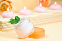 Moisturizing cream with candles Royalty Free Stock Photo