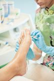 Moisturizing and massage feet pedicure procedure Stock Images