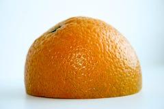 Moitié découpée en tranches par orange sur la surface Sur le fond blanc Photographie stock libre de droits