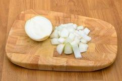 Moitié d'oignon et d'oignon coupé sur la plaque de découpage Photographie stock