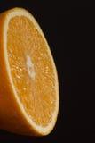 Moitié d'orange sur le fond foncé Photographie stock libre de droits