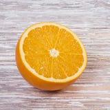 Moitié d'une orange sur une table en bois images libres de droits