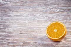 Moitié d'une orange sur une table en bois images stock