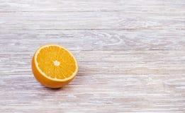 Moitié d'une orange sur une table en bois photographie stock libre de droits
