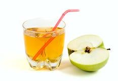 Moitié d'une pomme verte et une glace de jus de pomme Image stock