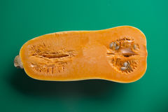 Moitié de courge de butternut, fond vert photographie stock