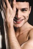 Moitié de dissimulation masculine heureuse de visage