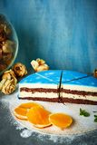 Moitié de gâteau cutted de mousse avec le lustre bleu sur une table concrète gris-foncé et le fond bleu Image stock