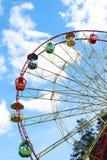 Moitié de grande roue et de dessus colorés des arbres et du ciel bleu Photos libres de droits