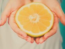 Moitié des agrumes jaunes de pamplemousse dans la main humaine Photographie stock