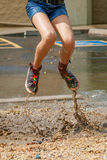 Moitié inférieure d'une fille sautant dans Muddy Puddle Image libre de droits