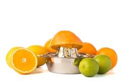 Moitié orange sur le presse-fruits en acier avec les agrumes entiers Photo libre de droits