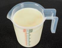 Moitié par litre de lait blanc dans une cruche transparente image libre de droits