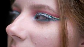 Moitié-portrait en gros plan de femme avec le maquillage coloré lumineux se déplaçant lentement sur le fond brouillé de lumières banque de vidéos