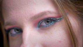 Moitié-portrait en gros plan de femme avec les yeux s'ouvrants de maquillage coloré lumineux lentement sur le fond brouillé de lu banque de vidéos