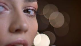 Moitié-portrait en gros plan de la belle fille caucasienne de brune observant mystérieusement dans la caméra sur les lumières bro photos libres de droits