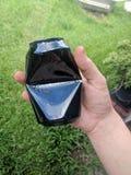 Moitié sans marque noire de boîte en aluminium écrasée tenue à la main image libre de droits