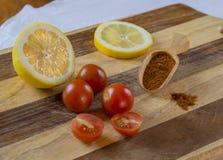 Moitié trois et deux des tomates-cerises avec le demi citron de citron slic Image stock
