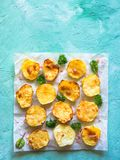 Moitiés cuites au four appétissantes de pommes de terre sur le parchemin image libre de droits