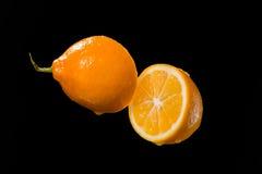 Moitiés de citron et baisses de jus d'isolement sur le fond noir du jus photos libres de droits