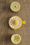Moitiés de citron et presse-fruits de citron Photo stock