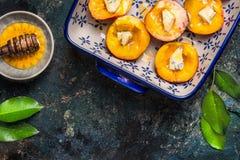 Moitiés des pêches avec du fromage et le miel dans le plat de cuisson sur le fond rustique foncé, vue supérieure Photos stock