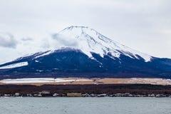 Moiunt富士身分高反对与漂浮在前面的一些蓬松云彩的阴暗天空 库存图片