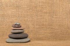 Mojón de piedra en fondo de la arpillera Fotos de archivo