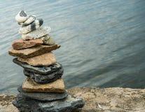 Mojón, piedras apiladas, en orilla del lago Foto de archivo