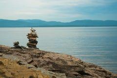 Mojón, piedras apiladas, en orilla del lago Imagen de archivo