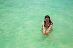 Moje a la mujer joven con el pelo largo estupendo en la agua de mar de la turquesa que sostiene estrellas de mar grandes en manos Fotos de archivo