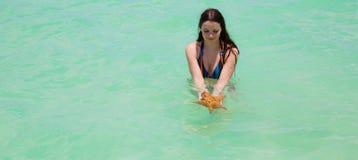 Moje a la mujer joven con el pelo largo estupendo en la agua de mar de la turquesa que sostiene estrellas de mar grandes en manos Imagen de archivo libre de regalías