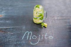 mojito玻璃与石灰和薄菏冰块特写镜头的在黑暗的木背景 免版税库存照片