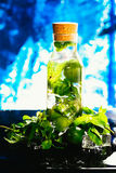 Mojito bottle with lime and mint ice cube close-up on blue background Royalty Free Stock Image