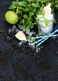 Mojito che cucina insieme Il mazzo di menta fresca, calce, ha scheggiato il ghiaccio ed il vetro del coctail sopra il contesto ne immagine stock libera da diritti