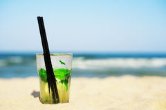 Mojito cocktail on the beach, blurred beach background. Sun, sun haze, glare Royalty Free Stock Images