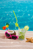 Mojito cocktail on beach sand with coconut and sunglasses Stock Images