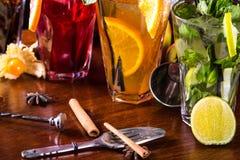 Mojito-cocktail da hortelã, cocktail alaranjado, cocktail da morango nos vidros de vidro com palhas Acessórios da barra: abanador imagem de stock