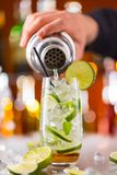 Mojito cocktail drink on bar counter. With barman holding shaker Royalty Free Stock Photos