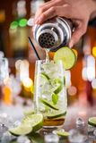Mojito cocktail drink on bar counter. With barman holding shaker on background stock image