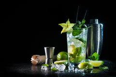 Mojito cocktail with fresh mint, lime, ice cubes and bar shaker. On dark background stock image