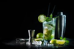 Mojito cocktail with fresh mint, lime, ice cubes and bar shaker. On dark background stock photos